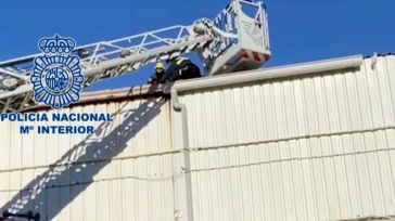 Un policía nacional auxilia a un MENA con una pierna fracturada en el tejado de una nave de El Tarajal